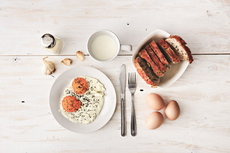 Top view of sunny side up breakfast eggs, sliced rye bread and hard boiled eggs. Banco de Imagens - 119384143
