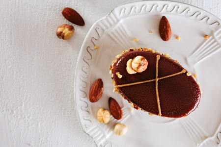 Delicious chocolate piece of cake with hazelnuts and almonds,on top of white ceramic plate,with copy space. View from above.