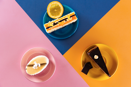 Colorful dessert table. Top view of coconut, orange white cream and dark chocolate hazelnut cakes on top of colorful dessert plates. Banco de Imagens