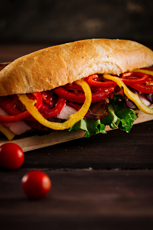 Close-up of homemade stuffed sandwich,against dark wooden background,with copy space available.