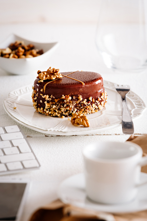 Delicious chocolate piece of cake with hazelnuts, on bright white working desk.