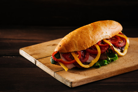 Delicious deli sandwich, filled with ham, cheese and vegetables, isolated on dark wooden background, with copy space next to it.