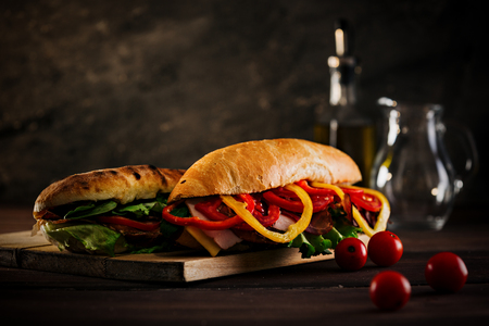 Hero shot of freshly prepared deli sandwiches on top of wooden plate,with cherry tomatoes in foreground and glassware in background. Banco de Imagens