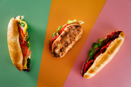Top view of a group of fresh deli sandwiches on top of colorful backgrounds.