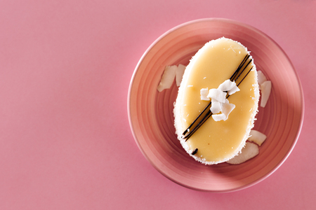 Top view of a delicious coconut homemade cake, placed on pink plate, on pink background.