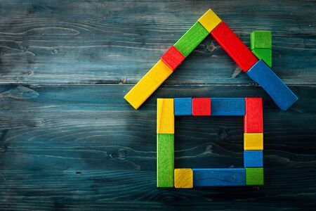 Insurance concept. Colorful wooden cubes in shape of house on top of the blue wooden board.