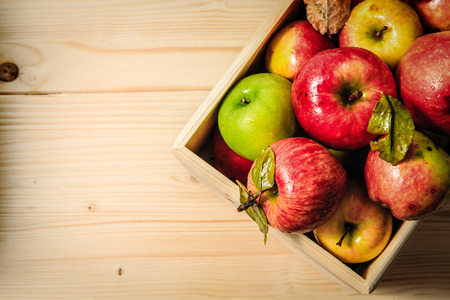 Top view of fresh organic apples inside wooden basket.
