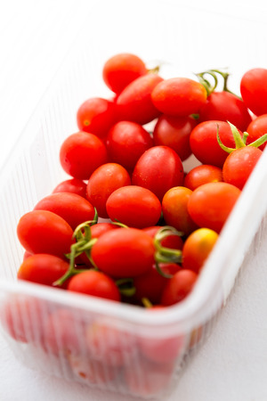 Fresh organic cherry tomatoes, inside plastic package, on white background. Banco de Imagens