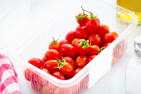 Fresh organic cherry tomatoes, in its own plastic package, on top of the kitchen table. Banco de Imagens