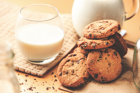 Close up of a tasty homemade cookies, next to glass of milk, on top of the wooden table.