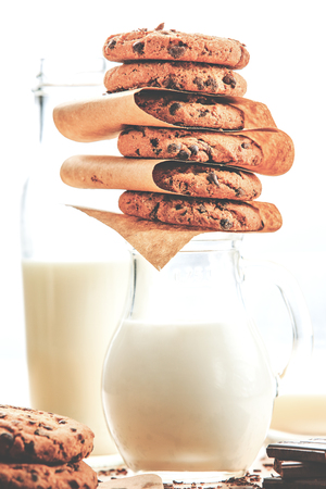 Close up of a tasty homemade cookies, on top of the milk glass carafe, next to open window on day light.