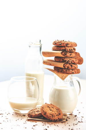Delicious snack. Lovely homemade cookies and milk, on top of the white table, next to window light.