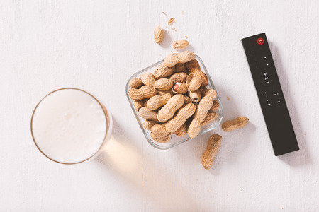 Its time for fun. Glass of beer, peanuts in shell and remote control on top of the white textured background.