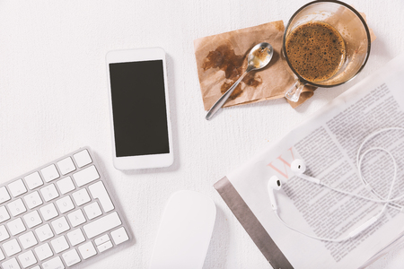 White smart phone, keyboard, newspaper and cup of coffee on top of the white wooden woking desk.
