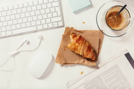 Modern working desk in the middle of the breakfast time. white business working objects, fresh croissant and cup of coffee. Top view. Banco de Imagens - 128572355