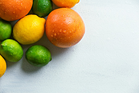 Organic and colorful citrus fruits on top of the white textured background.