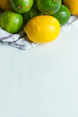 Top view of colorful fruits. Limes and lemon on white textured board.
