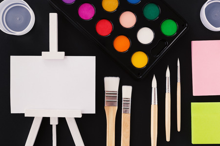 Lovely artistic concept. Colorful watercolor  palette, new wooden brushes, sticky notes and small white easel with paper on. Banco de Imagens - 119384390
