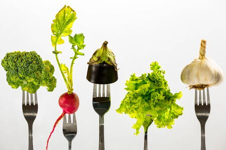 Various vegetables on top of the forks, against white background. Zdjęcie Seryjne