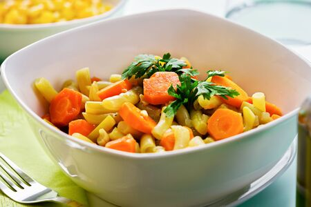 Served plate of mixed vegetarian lunch. Close up of green beans, carrots and spices. Stock Photo