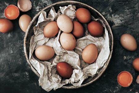 Top view of organic eggs inside rustic pan.