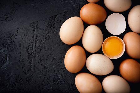 Organic chicken eggs on top of dark wooden background. Banco de Imagens