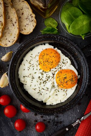 Close-up of sunny side up eggs with oregano on top of them, next to cherry tomatoes and rye bread.Top view.