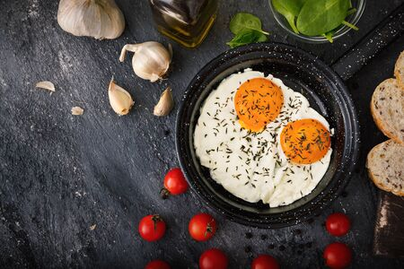 Sunny-side-up eggs with a pinch of oregano on top of them, next to cherry tomatoes, sliced rye bread and organic onions.View from above. Banco de Imagens
