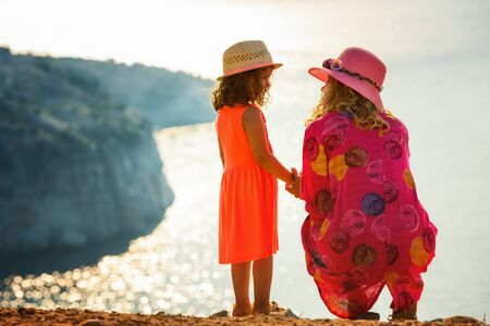 Mother and daughter talking and enjoying beautiful view of Mediterranean sea horizon.