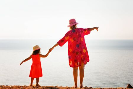 Mother and daughter enjoying beautiful mediterranean sea horizon view.