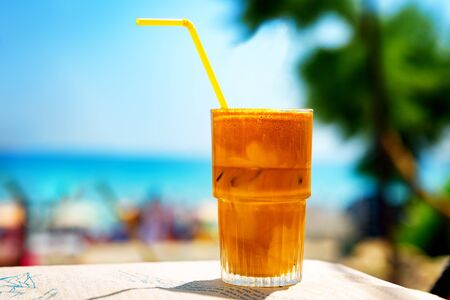 Iced coffee frappe at the beach cafe. Banco de Imagens - 128572399