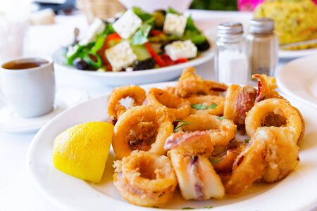 Close-up of fried squids, with greek salad and traditional greek coffee in background.