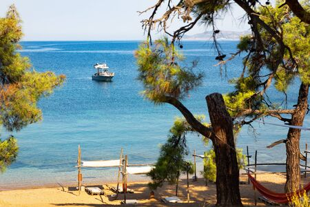 Secluded mediterranean sandy beach with  green woods in foreground and sea yacht in background.