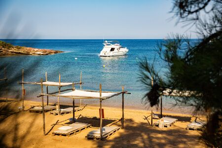 Secluded mediterranean sandy beach, with yacht at sea horizon.