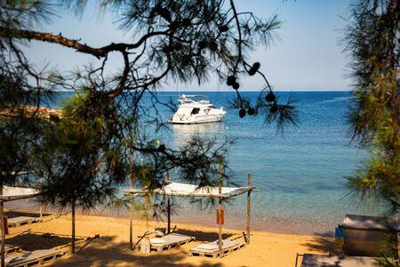 Beautiful mediterranean sandy beach with yacht on the sea horizon. Banco de Imagens