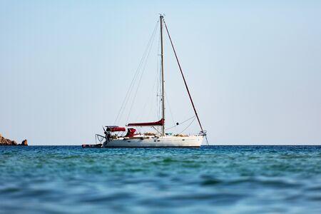 White sailing boat against sea horizon.