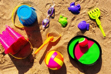 Colorful beach accessories for kids, laid flat on top of sand beach. Banco de Imagens
