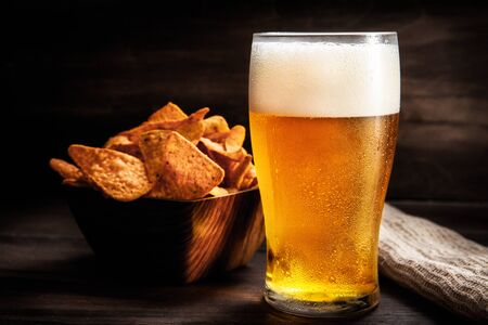 Beer and potato chips, on top of dark wooden background.