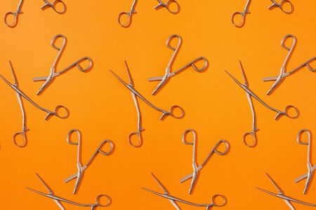 Surgical clamp and bandage scissor pattern on top of colorful background.