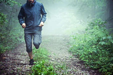 Close up of male athlete, wearing outdoor clothes, running through misty forest early in the morning. Copy space available.