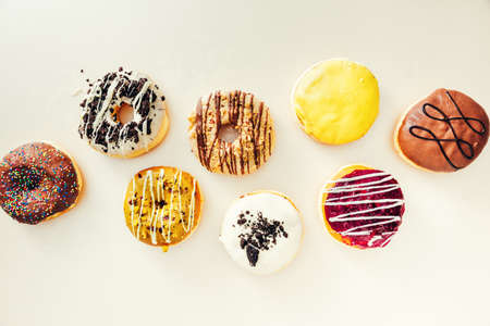 Various colorful creamy donuts with different glaze on top of them, isolated on white background. Stockfoto
