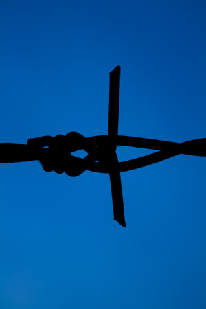 The silhouette of the barbed wire blue background Stock Photo
