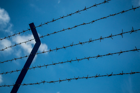 barblock: The rusty barbed wire fence and blue background Stock Photo