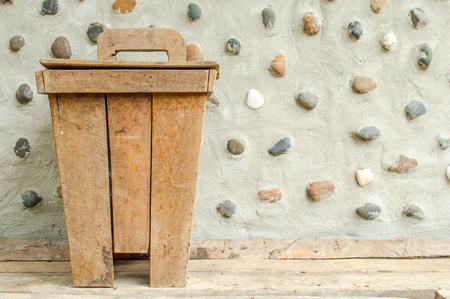 litterbin: The old wooden bin at cement wall decorate stone