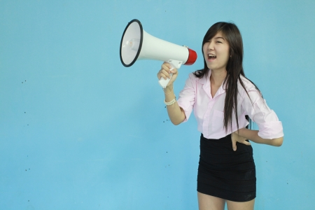 asia woman carry megaphone on blue background Stock Photo - 14570781