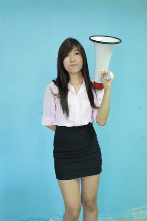 asia woman carry megaphone on blue background photo