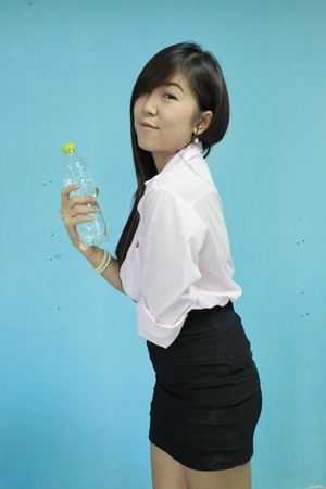 asia woman carry water bottle on blue background photo