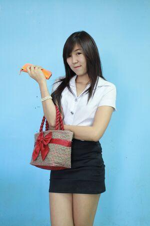 asia mujer lleva el bolso en uniforme de estudiante con el fondo azul Foto de archivo