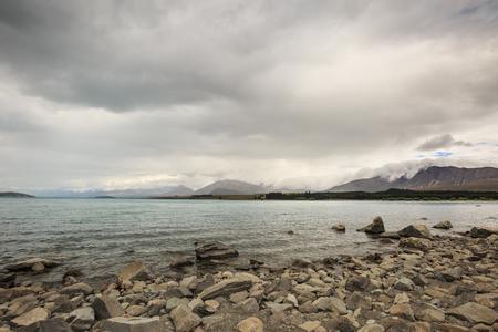 tekapo: a grey stone beach before rain come at lake tekapo