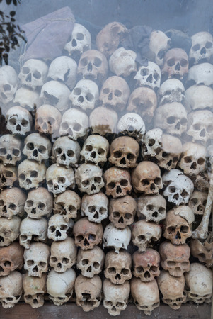 atrocity: A display of cracked human skulls, fading into shadow. These are the murder victims of the Khmer Rouge, found in the Killing Fields of Cambodia. A devastating reminder of the cruelty of man.